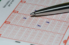 Playing lotto. Using a pen to fill out a lottery slip to play the lotto Royalty Free Stock Image