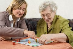 Playing ludo. Grandmother and granddaughter playing ludo stock photo