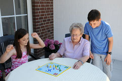 Playing ludo with grandma. Young and old, grandchildren playing  ludo  with  their ninety years old grandma Stock Image