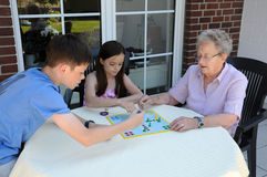 Playing ludo with grandma. Young and old, grandchildren playing  ludo  with  their ninety years old grandma Stock Photo