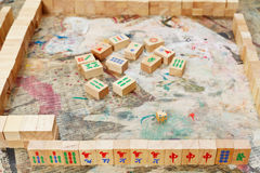 Playing in mahjong desk game by wooden tiles. On shabby table stock photography