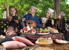 Playing mandolin during breakfast. The head of the family playing mandolin during breakfast. Whole family dressed in Central Asian clothes Royalty Free Stock Photography