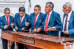 Playing marimba, Cuidad Vieja, Guatemala. Cuidad Vieja, Guatemala - December 7, 2017: Local marimba band plays outside church celebrating Our Lady of the Royalty Free Stock Images