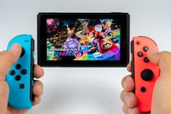 Playing Mario Kart Deluxe 8 in Nintendo Switch Royalty Free Stock Image