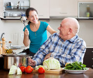 Playing mature couple cooking food Royalty Free Stock Photos