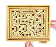 Playing Maze Game. Player guiding red marble round maze game while trying to avoid holes Royalty Free Stock Photography