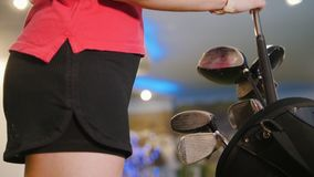 Playing mini golf. A young blonde woman comes to the bag and taking a golf stick. Mid shot stock footage