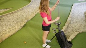 Playing mini golf. A young blonde woman comes to the bag and taking a golf stick. Upper view stock video