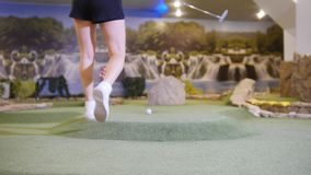 Playing mini golf. A young woman playing mini golf indoors. Coming closer to the ball, hit it and it gets in the hole. Mid shot stock video footage