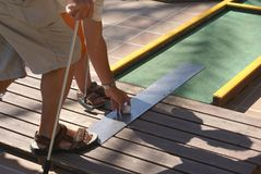 Playing miniature golf. Miniature golf, minigolf, crazy golf, or put putt golf, is an offshoot of the sport of golf focusing on the putting aspect of its parent Royalty Free Stock Image