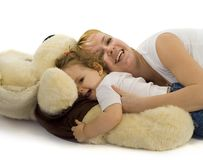 Playing with mom 2. Young mother playing with her baby girl and a giant plush dog stock photography