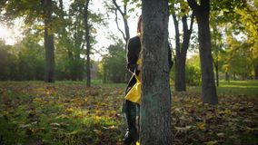 Playing with mom, an amazing smiling girl plays in autumn park with her parent hiding behind tree trunk during family