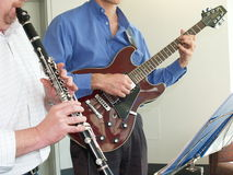 Playing Music. Playing the Clarinet and Bass Guitar Royalty Free Stock Photo