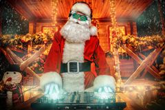 Playing music at christmas. DJ Santa Claus in luminous glasses and headphones holds a party near his house decorated with lights. Christmas songs and music stock photo