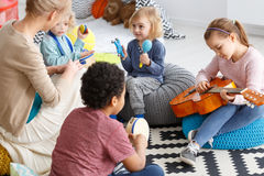Playing the music. Group of little children playing music in kindergarten Royalty Free Stock Image