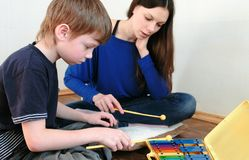 Playing music instrument. Boy repeats for the teacher playing the notes on the xylophone. royalty free stock photos