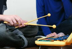 Playing music instrument. Closeup boy`s hand playing on xylophone and his mom sitting near him. Playing music instrument. Closeup boy,s hand playing on Stock Photography