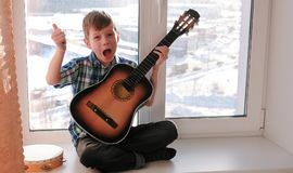Playing a musical instrument. Boy plays the guitar and singing sitting on the windowsill. royalty free stock photo