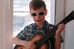 Playing a musical instrument. Boy in sunglasses plays the guitar sitting on the windowsill. royalty free stock photo