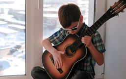 Playing a musical instrument. Boy in sunglasses plays the guitar sitting on the windowsill. stock images