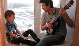 Playing a musical instrument. Dad is playing the guitar and son is playing tambourine sitting in windowsill. stock image