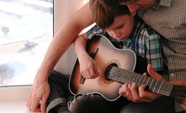 Playing a musical instrument. Dad teaches his son to play the guitar, sitting on the windowsill. Playing a musical instrument. Dad teaches his son to play the stock photos