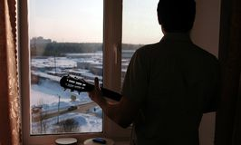 Playing a musical instrument. Man`s silhouette playing the guitar near windowsill. Playing a musical instrument. Man`s silhouette playing the guitar near royalty free stock photography