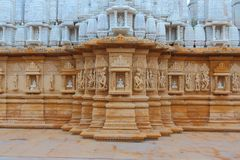 Artistic carving on red and white stone, shankheshwar parshwanath, jain temple, gujrat, India. Playing musical instruments and wearing beautiful  jewelry Royalty Free Stock Photo