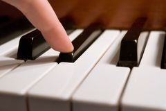 Playing a Note. One finger playing the piano - selective focus on the finger royalty free stock images