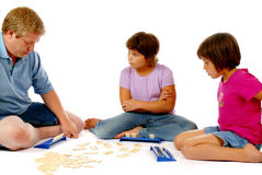 Playing a Numbers Game. Face-on view of father and daughters playing an educational numbers game.  Iolated on white Stock Photos