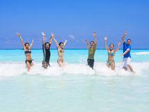 Playing in the Ocean Waves. A group of young adults playing together in the ocean. Jumping with the waves is fun Royalty Free Stock Image