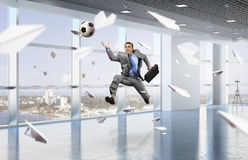 Playing office soccer . Mixed media Royalty Free Stock Image