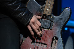 Playing old bass guitar. Rock concert: hand of musician, playing old bass guitar Stock Photography