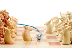 Playing an online game. Blue ethernet cable running between an active game of chess, playing out on line games Royalty Free Stock Images