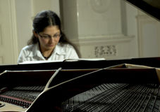 Playing An Open Baby Grand. Portrait of a female piano teacher looking downward as she plays grand piano.  Taken from across open piano top.  Piano is in focus Stock Photo
