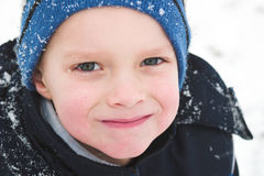 Playing outside in the winters. A child smiles as he has the time of his life playing in the snow stock photos
