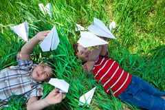 Playing with paper planes on grass royalty free stock image