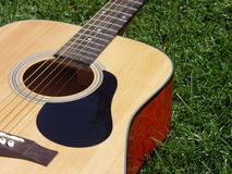 Playing in the Park. Guitar sitting in the grass waiting to be played Stock Image