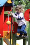 Playing at the park. Young boy playing on a climbing frame in the park Stock Image