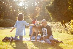 Playing in the park with their dog. Animal lovers. Mother, father, daughter and their dog Stock Photo
