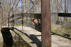 Playing peek-a-boo on the bridge. Redheaded boy playing peek-a-boo on an old bridge Royalty Free Stock Images