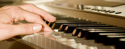 Playing the piano. A woman's hand playing the piano Stock Photos