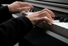 Playing piano. A closeup of a pair of hands as they press on piano keys Royalty Free Stock Photos