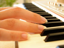 Playing the piano. Close-up of a womans hand playing the piano Stock Photo