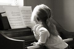 Playing the piano. A little girl learning to play the piano Stock Images