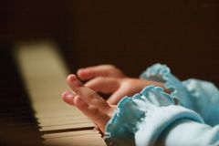Playing the piano. Hands of a little girl playing the piano - grainy image