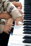 Playing piano. Mother's hands and child's hands are playing piano Stock Image