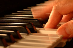 Playing piano. Details of the keys and a hand while playing piano Royalty Free Stock Photo