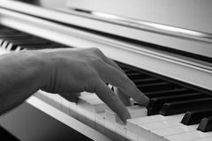 Playing Piano 2. Closeup on a hand playing the piano Stock Photo