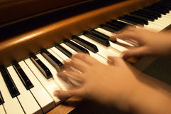 Playing the Piano. A musician's hands in blur-motion while playing the piano Stock Images